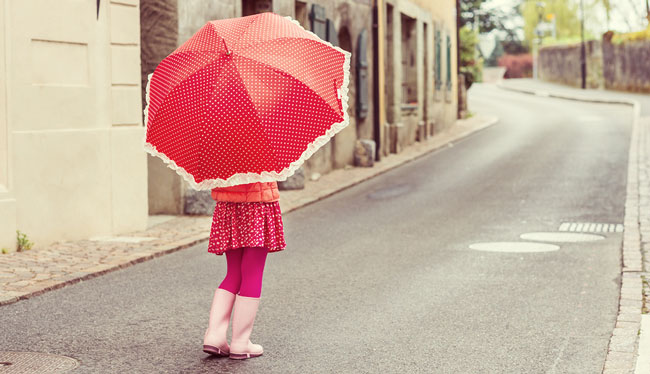 girl wearing light pink rain boots and pink clothes with a pink polkadot umbrella